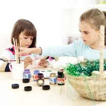 Two Girls (6-8) Painting Easter Eggs on a Table